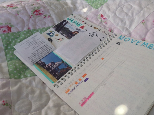 An open double page of a otebook. On the left a scrapbook page for Japan with a photo of a golden pavilion, stickers, and tickets stuck in. On the right a page for November with long rectangles for each day of the month, some of which are marked off with colours.