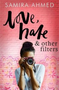 Cover of Love, Hate & other filters by Samira Ahmed. A person with brown skin and dark hair in a bun taking a photo with the camera pointed at the reader. They stand in front of a red wall with colourful tessellating patterns at the bottom. The title and author above.
