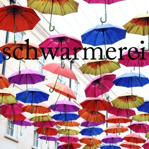 Many umbrellas of different colours suspended in the air along a street. The word 'schwarmerei' on top.