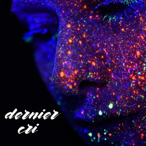 A face that is covered with glow in the dark paint spots and glitter. The words 'dernier cri' in brush font.