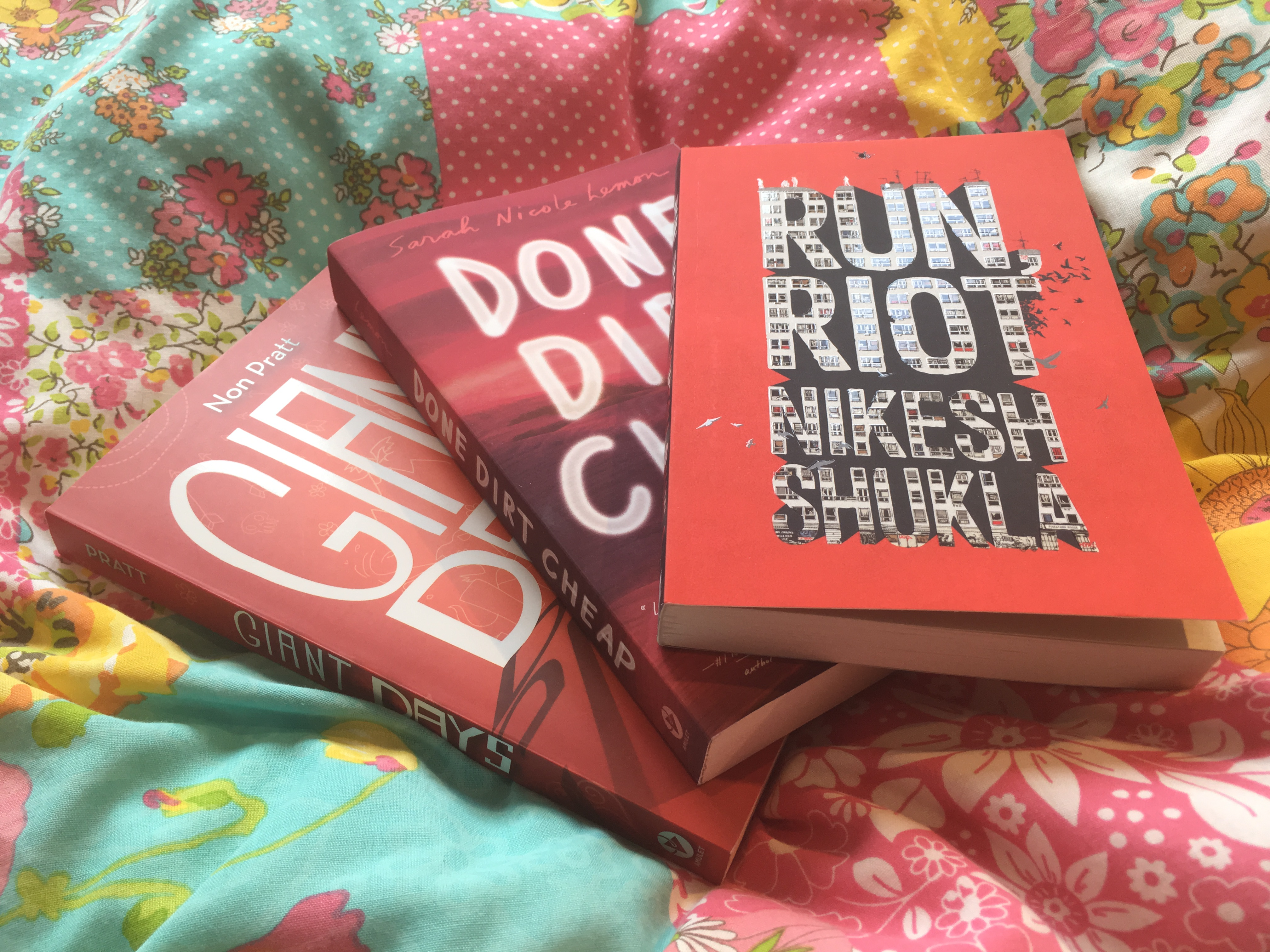 The books Giant Days, Done Dirt Cheap and Run, Riot spread out on a flowery duvet.