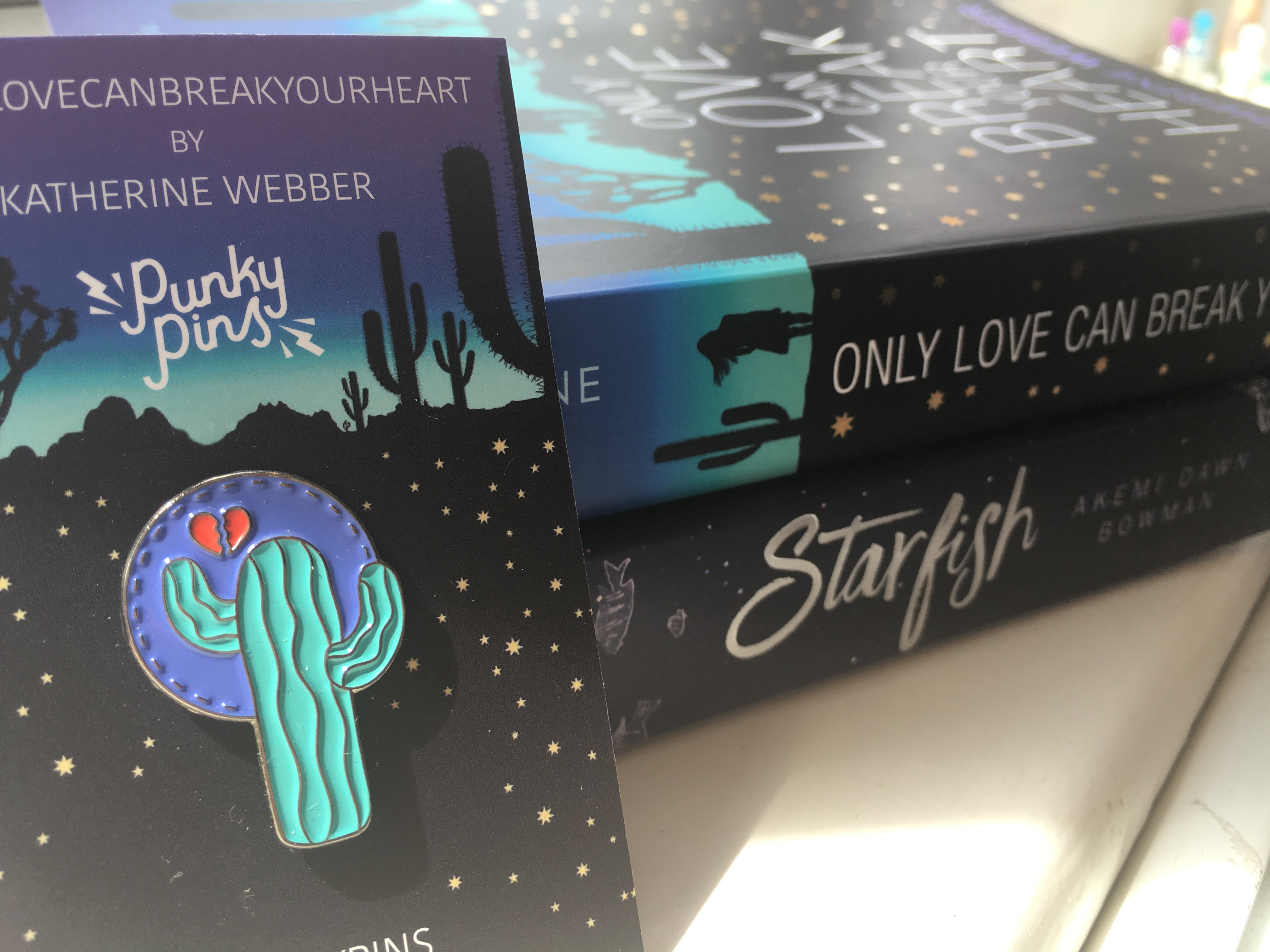 The spines of the books Only Love Can Break Your Heart and Starfish. An enamel pin with a cactus and a broken heart is in the foreground.