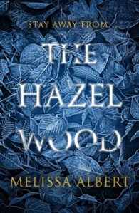 Cover of The Hazel Wood. The title is covered over by silvery-blue leaves. The text reads 'Stay away from... the Hazel Wood.'